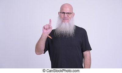 Happy mature bald bearded man smiling while pointing up -...