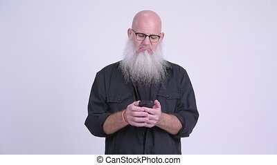 Happy mature bald bearded man smiling while using phone