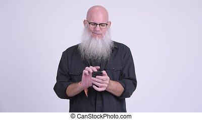 Happy mature bald bearded man thinking while using phone