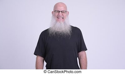 Happy mature bald bearded man with eyeglasses smiling -...
