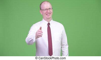 Happy mature bald businessman giving handshake - Studio shot...