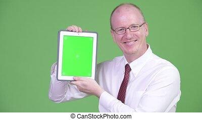 Happy mature bald businessman showing digital tablet -...