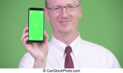 Happy mature bald businessman showing phone - Studio shot of...