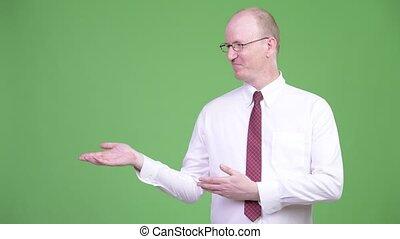 Happy mature bald businessman showing something - Studio...