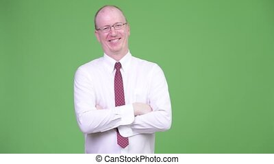 Happy mature bald businessman with arms crossed