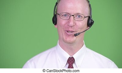 Happy mature bald businessman working as call center...