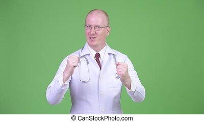 Happy mature bald man doctor looking excited - Studio shot...