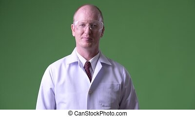 Happy mature bald man doctor wearing protective glasses -...