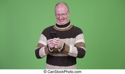 Happy mature bald man with turtleneck sweater using phone