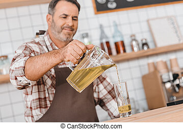 bartender pouring apple juice in glass