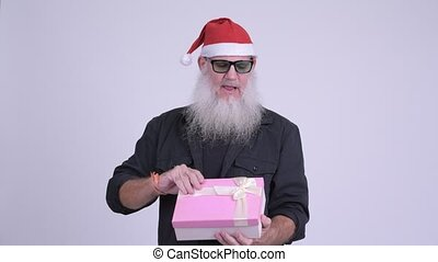 Happy mature bearded hipster man opening gift for Christmas...