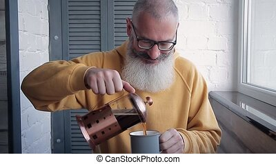 Happy mature bearded man pours too much coffee into cup and holds out drink to camera. Blurred kitchen background.