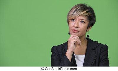 Happy mature beautiful multi-ethnic businesswoman thinking -...