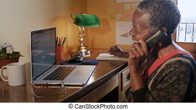 Happy mature black woman hanging up her cordless phone at...