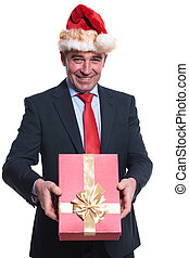 happy mature business man with santa hat is giving you a present on white background