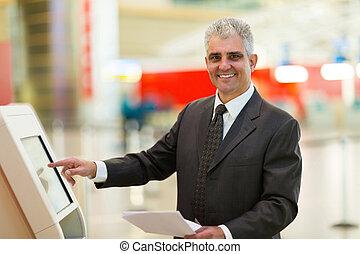 mature businessman using self help check in machine - happy ...