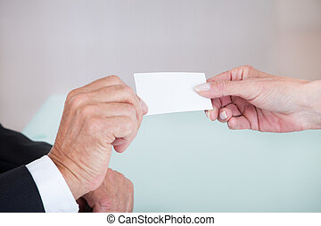Businesspeople Exchanging Visiting Card In Office