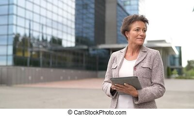 Happy Mature Businesswoman Thinking While Using Digital...