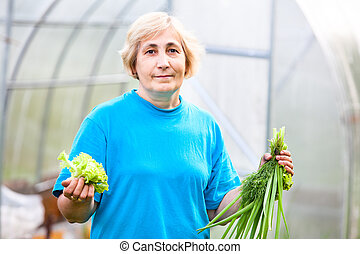 Happy mature Caucasian woman with onion and lettuce in front of the greenhouse