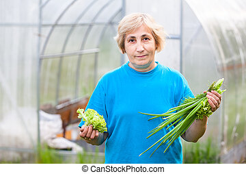 Happy mature Caucasian woman with onion and lettuce in the garden