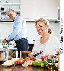 happy mature couple cooking vegetables