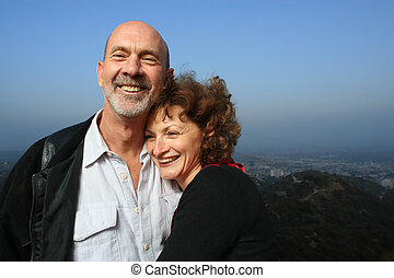 Happy mature couple embracing outdoors ontop of a city.