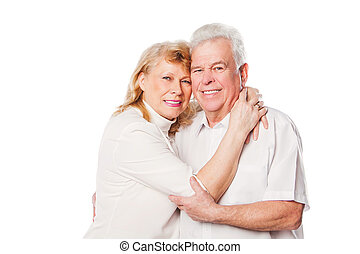 Happy mature couple embracing smiling at camera on white background