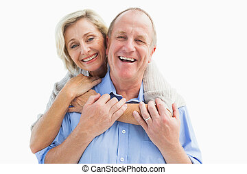 Happy mature couple embracing smiling at camera on white...