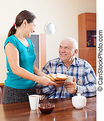 Happy mature couple having breakfast