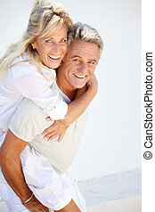 Happy mature couple having fun over white background.