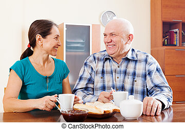 Happy mature couple having tea