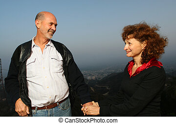 Happy mature couple holding hands outdoors ontop of a city at sunset.