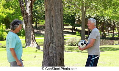 Happy mature couple playing with a soccer ball in the...