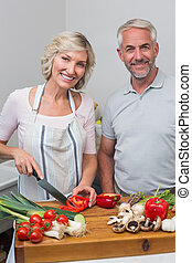 Happy mature couple preparing food in kitchen