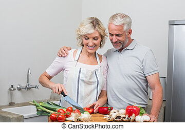 Happy mature couple preparing food together in kitchen