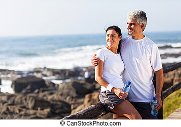 mature couple relaxing after exercise - happy mature couple...