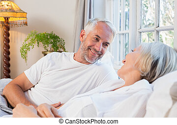 Happy mature couple relaxing in bed
