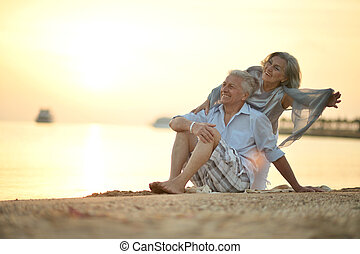 Happy Mature couple relaxing on beach at sunset