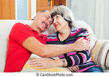 Happy mature couple relaxing on couch