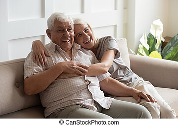 Happy mature couple resting on couch looking at camera - ...