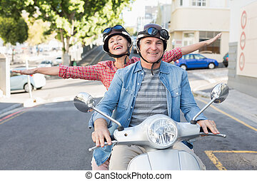 Happy mature couple riding a scooter in the city on a sunny...