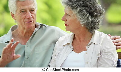 Happy mature couple sitting next to their picnic basket