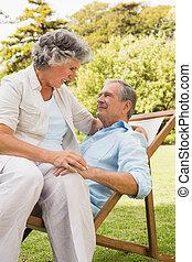 Happy mature couple sitting on sun lounger