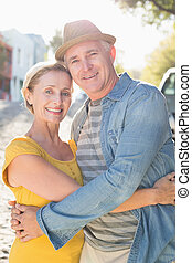 Happy mature couple smiling at camera in the city