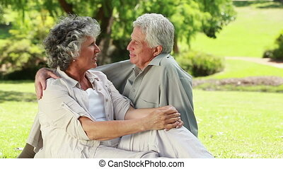 Happy mature couple talking while sitting on the grass
