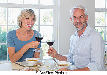 Happy mature couple toasting wine glasses over food