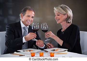 Happy Mature Couple Toasting Wine In A Elegant Restaurant