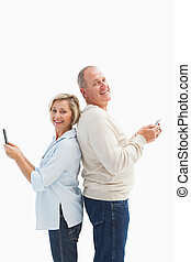Happy mature couple using their smartphones on white...