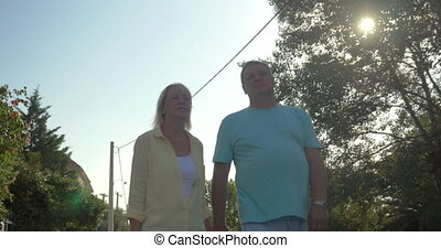 Happy Mature Couple Walking in Country Town