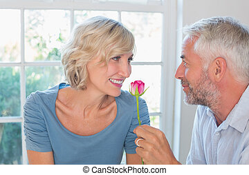 Happy mature couple with a flower